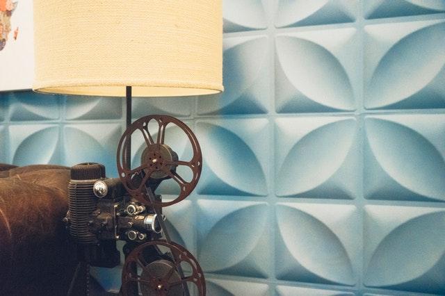 Lampa vyrobená zo starej kamery vedľa koženého gauča a steny s modrým obkladom