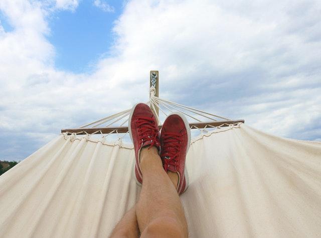 Človek ležiaci v hojdacej sieti s vyloženými nohami